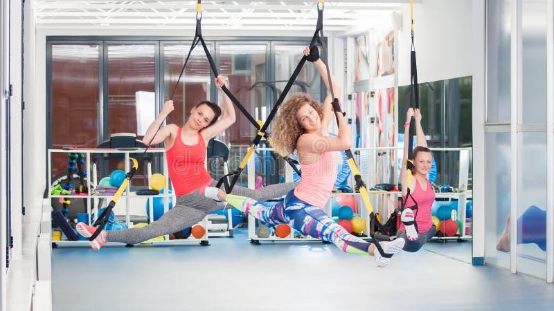 Grupo de jovens mulheres bonitas que fazem o exercício em TRX foto de stock royalty free