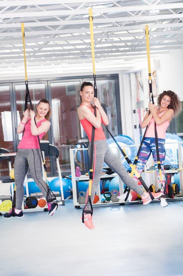 Grupo de jovens mulheres bonitas que fazem o exercício em TRX imagens de stock royalty free