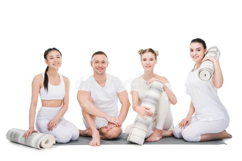 Grupo de jovens mulheres de sorriso com o instrutor que senta-se junto com esteiras da ioga fotos de stock royalty free