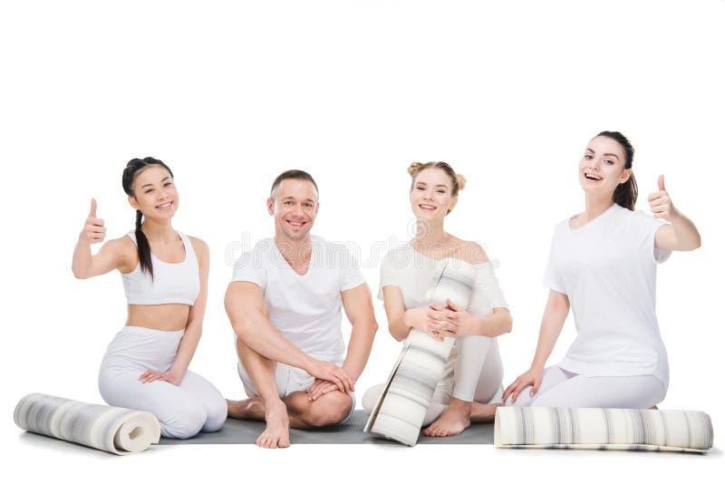 Grupo de jovens mulheres de sorriso com o instrutor que senta-se junto com esteiras da ioga imagem de stock