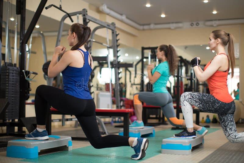 Grupo de jovens mulheres que dobram os músculos no gym Conceito do esporte, da aptidão, da saúde e do estilo de vida foto de stock