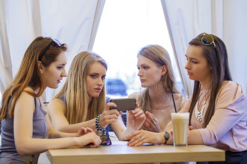 Grupo de jovens mulheres que sentam-se em torno da tabela que come a sobremesa imagem de stock