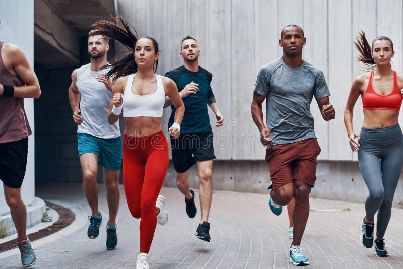 Grupo de jovens na roupa dos esportes fotografia de stock
