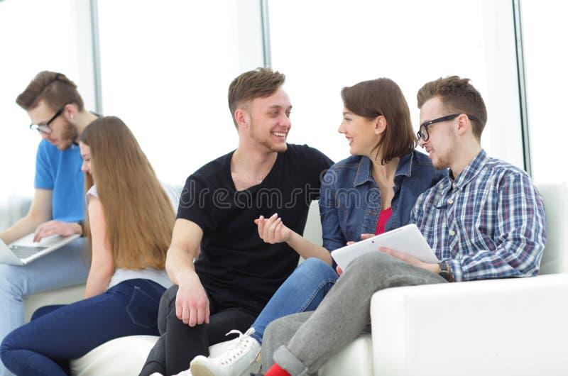 Grupo de jovens na roupa ocasional que conversam e que têm o divertimento fotografia de stock royalty free