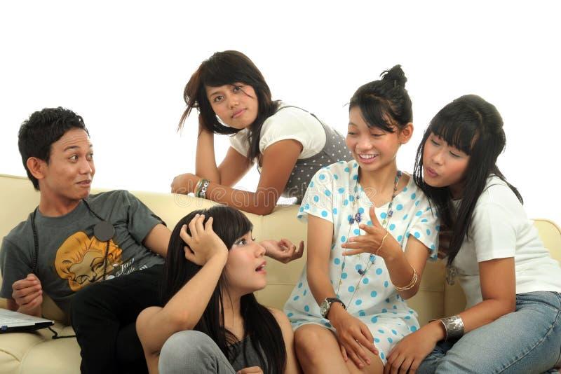 Grupo de jovens no sofá imagens de stock