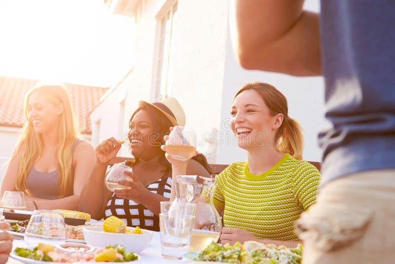 Grupo de jovens que apreciam a refeição exterior do verão imagens de stock