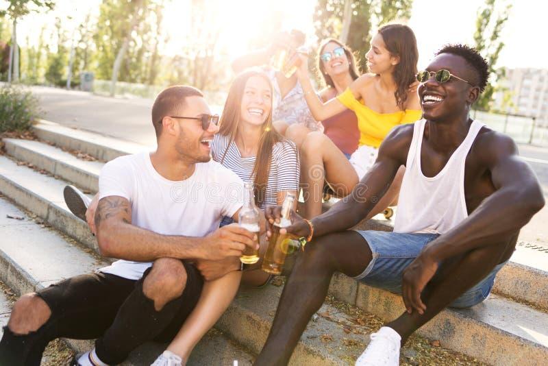 Grupo de jovens que brindam com cerveja em uma área urbana fotografia de stock