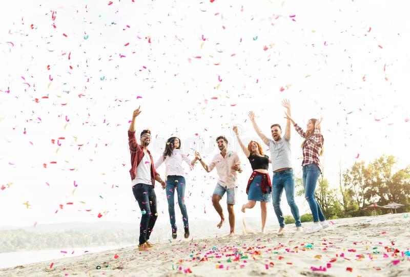 Grupo de jovens que comemoram na praia imagem de stock