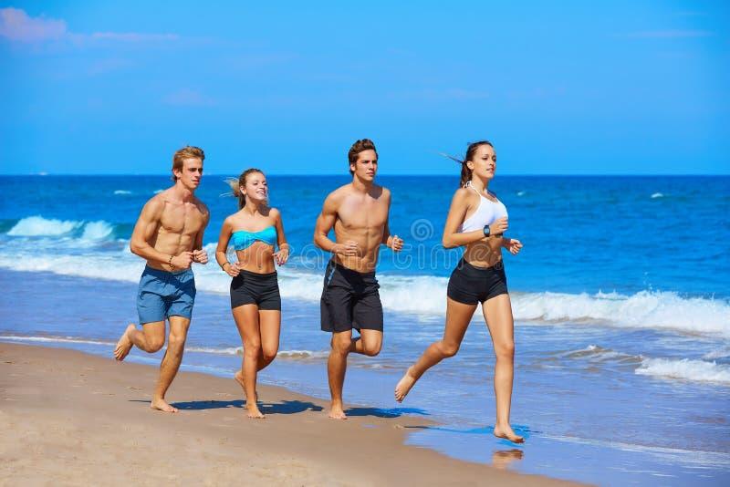 Grupo de jovens que correm na praia imagens de stock