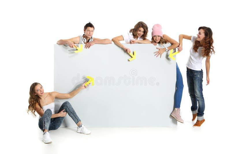 Grupo de jovens que guardam uma placa branca vazia com espaço para o texto fotografia de stock