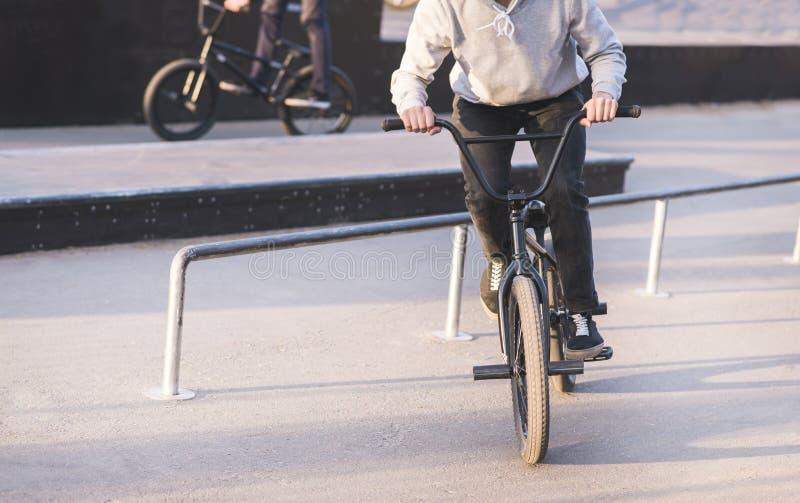 grupo de jovens que montam um parque do patim em uma bicicleta do bmx e que fazem truques Truques de formação no bmx fotografia de stock royalty free