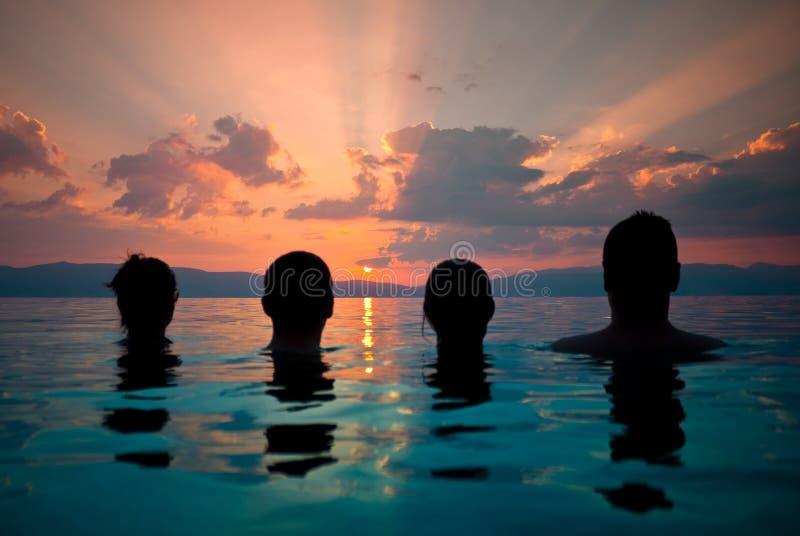 Grupo de jovens que olham o por do sol imagem de stock royalty free