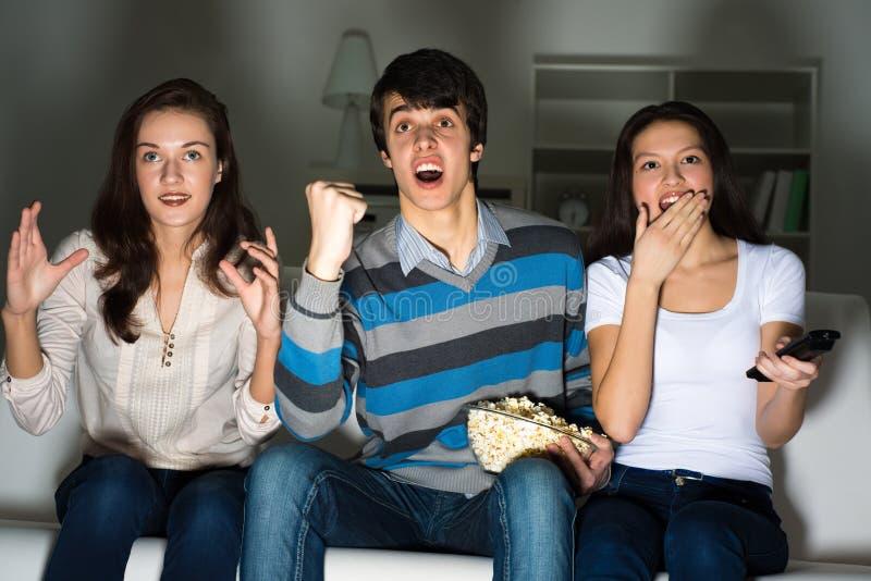 Grupo de jovens que olham a tevê no sofá imagem de stock