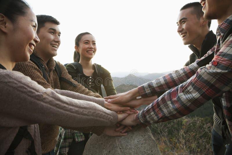 Grupo de jovens que sorriem e que mantêm as mãos unidas na pedra imagem de stock royalty free