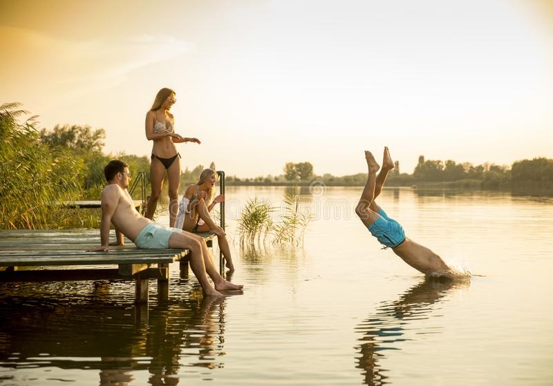 Grupo de jovens que t?m o divertimento no cais no lago foto de stock