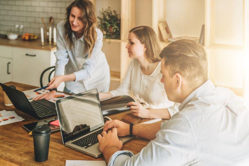 Grupo de jovens que trabalham junto O homem está usando o portátil, meninas que olham na tela do portátil, discutindo o plano de  imagem de stock royalty free
