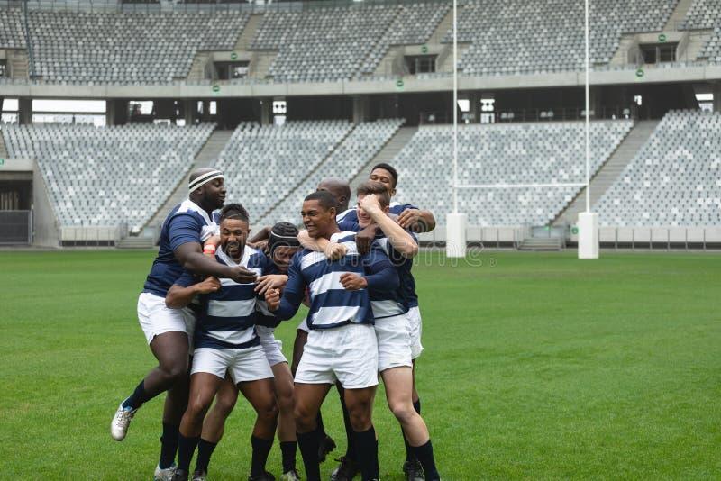 Grupo de jugadores masculinos diversos del rugbi que celebran meta en estadio foto de archivo