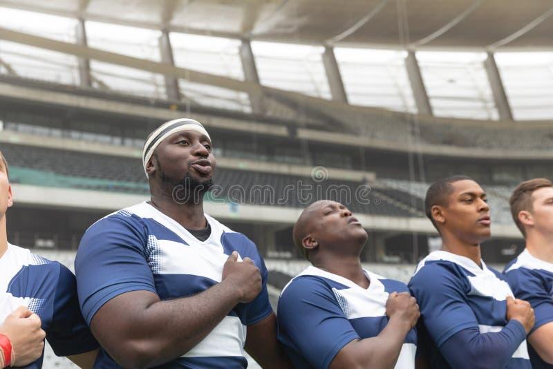 Grupo de jugadores masculinos diversos del rugbi que toman compromiso junto en estadio imagen de archivo