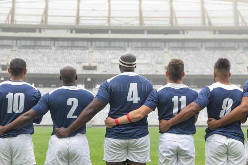 Grupo de jugadores masculinos diversos del rugbi que toman compromiso junto en estadio foto de archivo