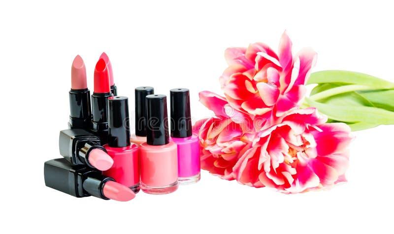Grupo de lápices labiales coloridos, esmaltes de uñas y tulipanes aislados imagen de archivo
