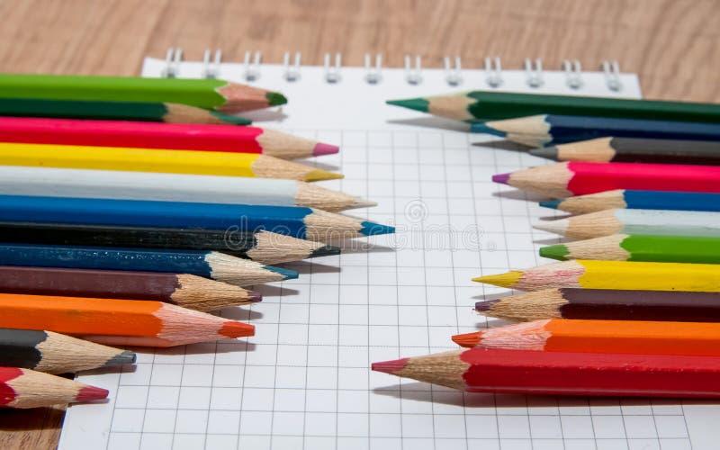 Grupo de lápis coloridos que encontram-se na fileira no Livro Branco imagens de stock royalty free