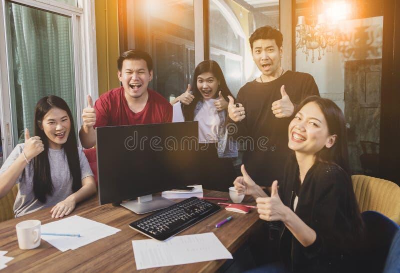 Grupo de la emoción más joven asiática i de la felicidad del trabajo del equipo que trabaja independientemente imagen de archivo libre de regalías