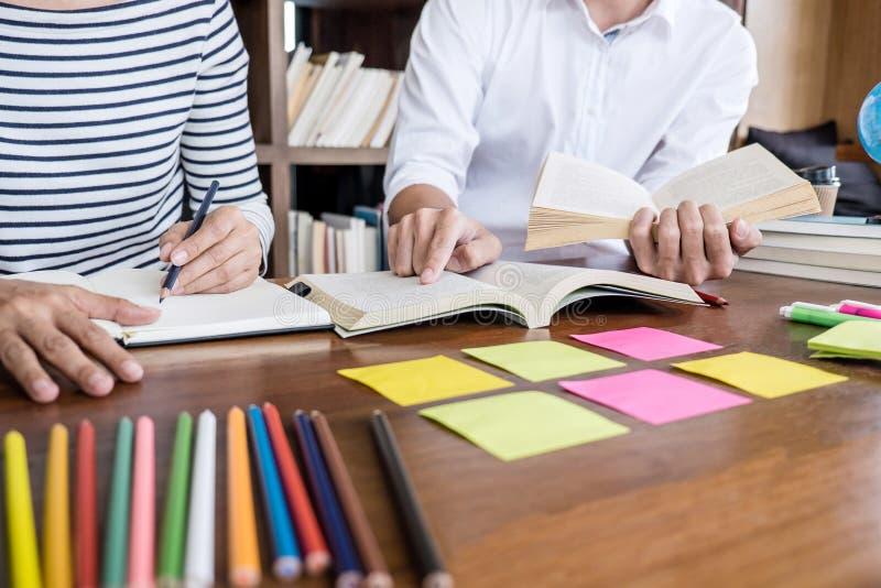 Grupo de la escuela secundaria o de estudiante universitario que se sienta en el escritorio en la biblioteca que estudia y que le imagen de archivo libre de regalías