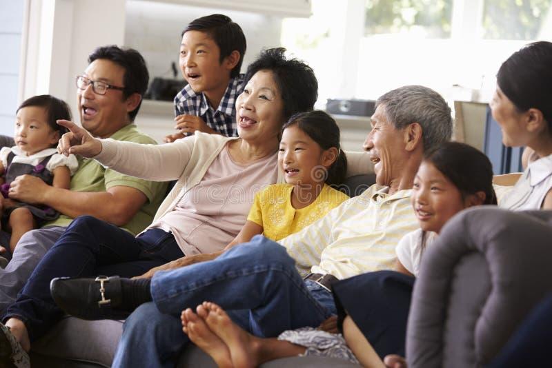 Grupo de la familia extensa en casa que ve la TV junto imagen de archivo
