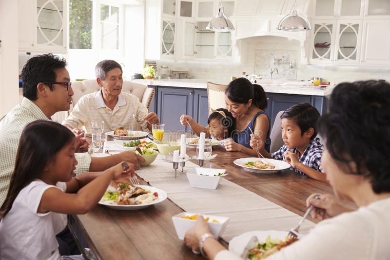 Grupo de la familia extensa que come la comida en casa junto fotos de archivo