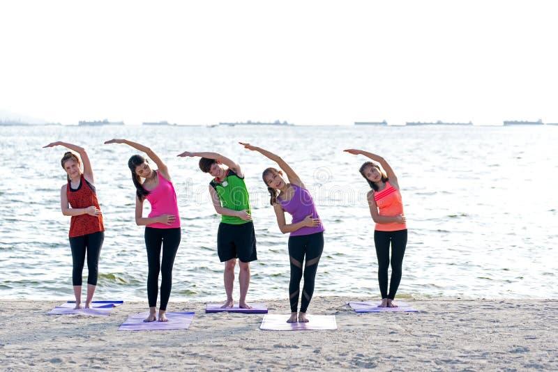 Grupo de la gente de Asia que hace que el guerrero presenta en la playa, la aptitud, el deporte, la yoga y la forma de vida sana imagen de archivo libre de regalías