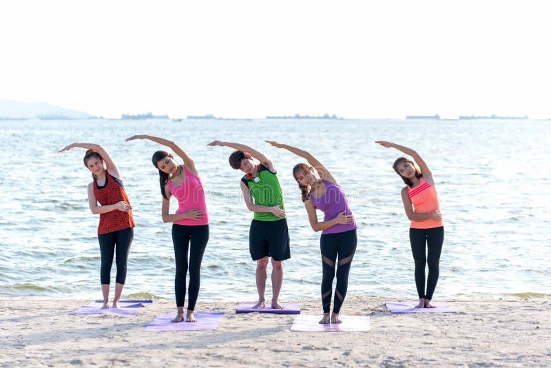 Grupo de la gente de Asia que hace que el guerrero presenta en la playa, la aptitud, el deporte, la yoga y la forma de vida sana imagenes de archivo