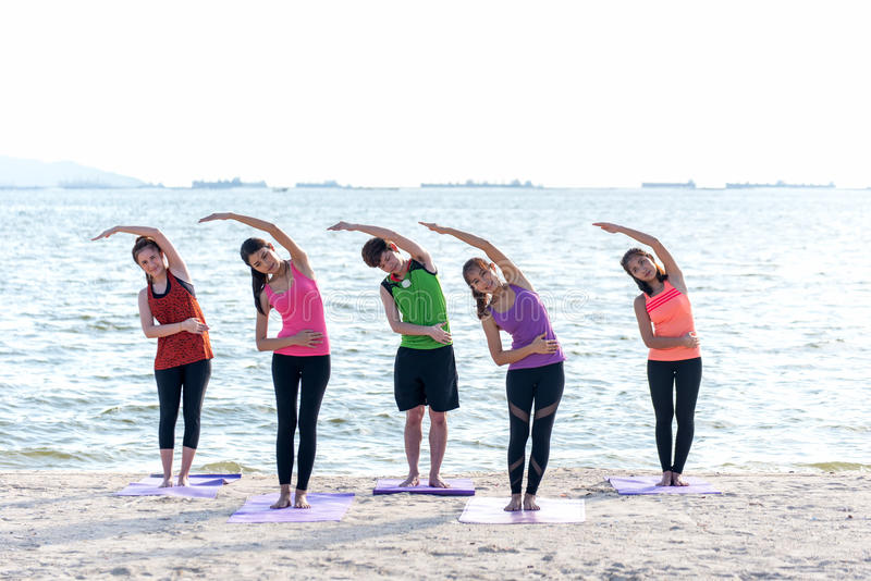 Grupo de la gente de Asia que hace que el guerrero presenta en la playa, la aptitud, el deporte, la yoga y la forma de vida sana imágenes de archivo libres de regalías