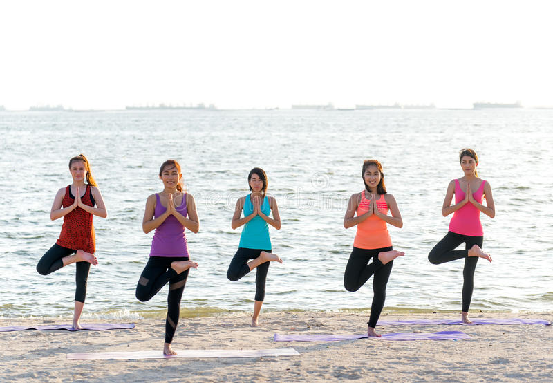 Grupo de la gente de Asia que hace que el guerrero presenta en la playa, la aptitud, el deporte, la yoga y la forma de vida sana foto de archivo libre de regalías