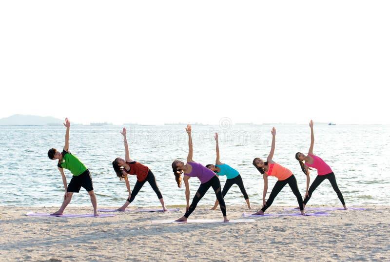 Grupo de la gente de Asia que hace que el guerrero presenta en la playa, la aptitud, el deporte, la yoga y la forma de vida sana fotografía de archivo