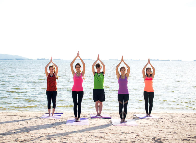 Grupo de la gente de Asia que hace que el guerrero presenta en la playa, la aptitud, el deporte, la yoga y la forma de vida sana fotos de archivo