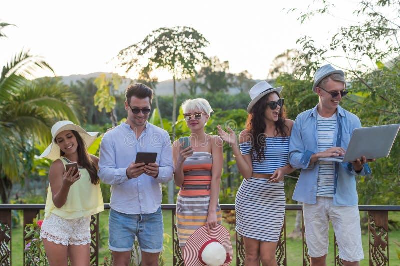 Grupo de la gente joven en el hotel tropical de la terraza, amigos que usan vacaciones tropicales del día de fiesta del teléfono  imagenes de archivo