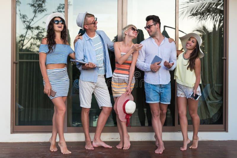 Grupo de la gente joven en el hotel tropical de la terraza, amigos que usan vacaciones tropicales del día de fiesta del teléfono  fotografía de archivo libre de regalías