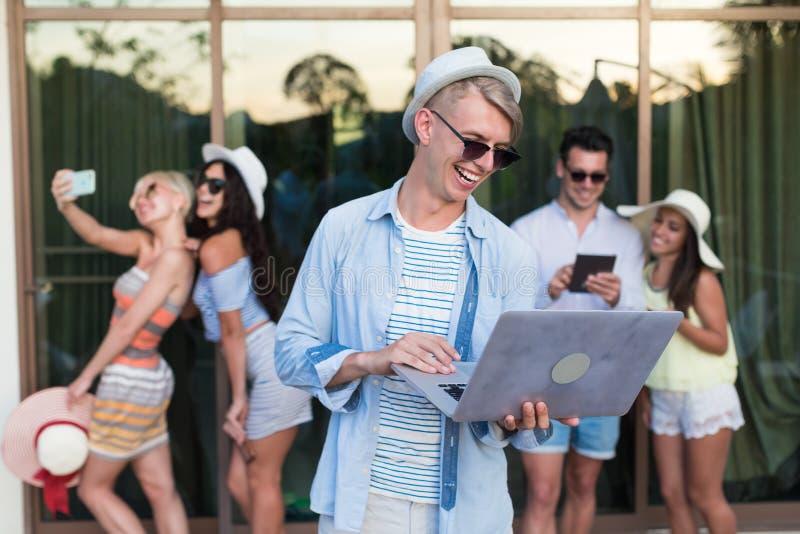 Grupo de la gente joven en el hotel tropical de la terraza, amigos que usan vacaciones tropicales del día de fiesta del teléfono  foto de archivo