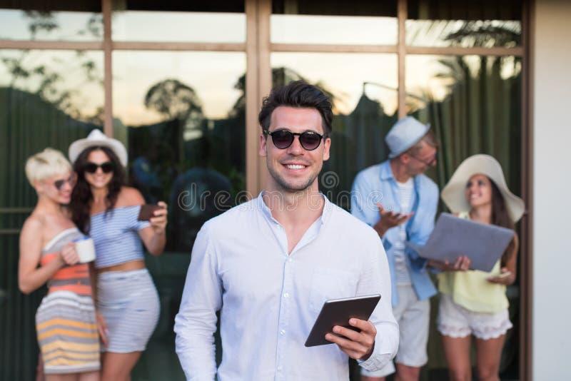 Grupo de la gente joven en el hotel tropical de la terraza, amigos que usan vacaciones tropicales del día de fiesta del teléfono  fotos de archivo libres de regalías