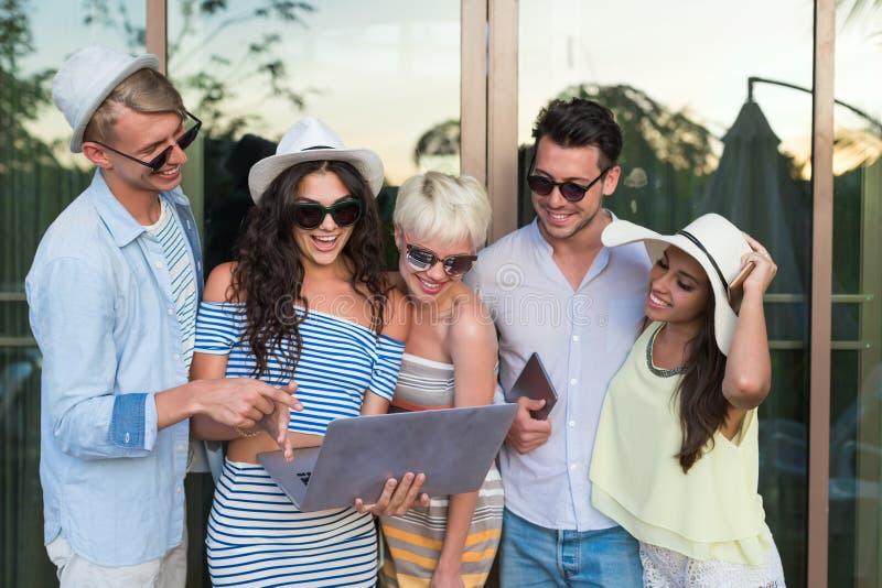 Grupo de la gente joven en el hotel tropical de la terraza, amigos que usan vacaciones tropicales del día de fiesta del teléfono  foto de archivo libre de regalías