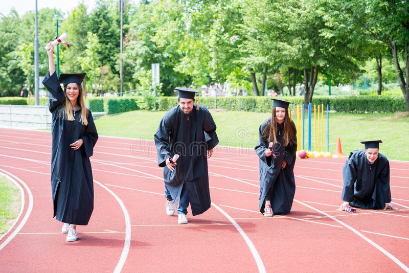 Grupo de la graduación de estudiantes que celebran en la pista atlética, preparación imagen de archivo