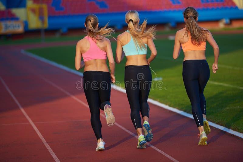 Grupo de la mujer del atleta que corre en circuito de carreras del atletismo fotos de archivo libres de regalías