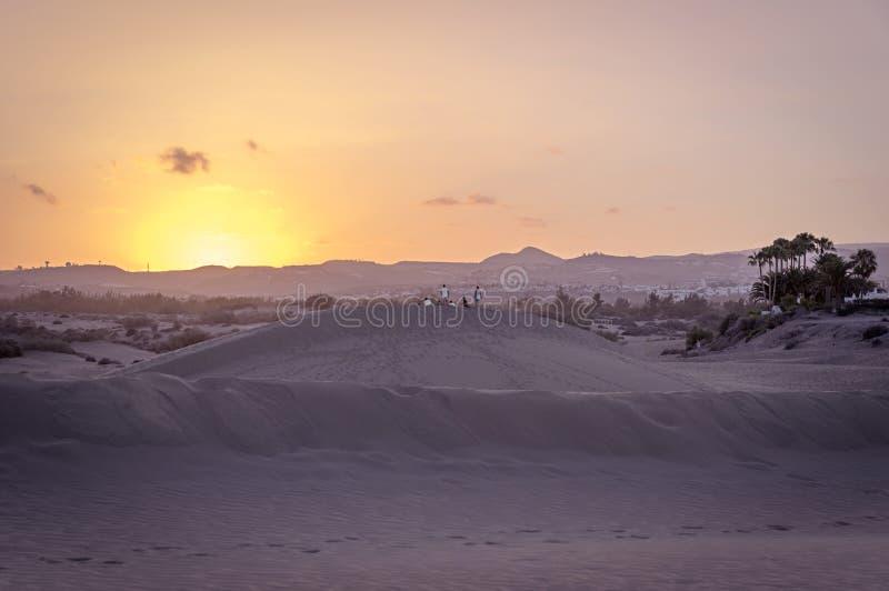 Grupo de la puesta del sol de observación en las dunas de Maspalomas, G de la gente joven fotos de archivo