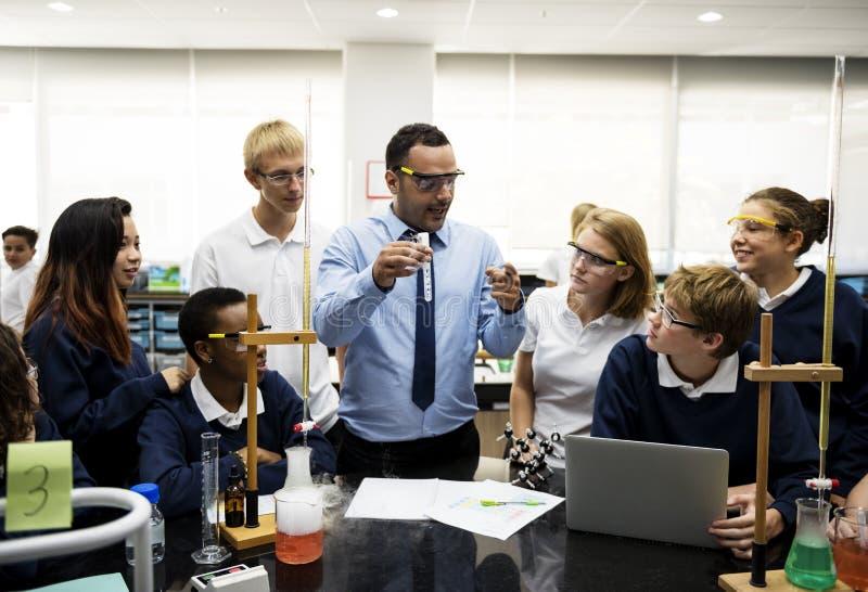 Grupo de laboratorio del laboratorio de los estudiantes en sala de clase de la ciencia imagen de archivo libre de regalías
