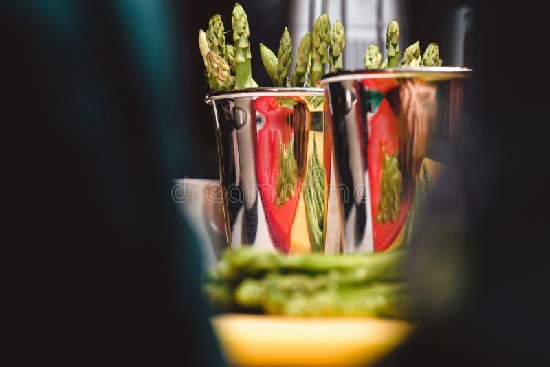 Grupo de lanças verdes frescas do aspargo na reflexão da sagacidade da cubeta do cromo tiro macro do foco seletivo com DOF raso foto de stock royalty free
