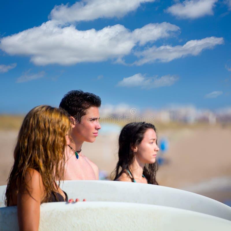 Grupo de las personas que practica surf del adolescente feliz en orilla de la playa fotos de archivo libres de regalías