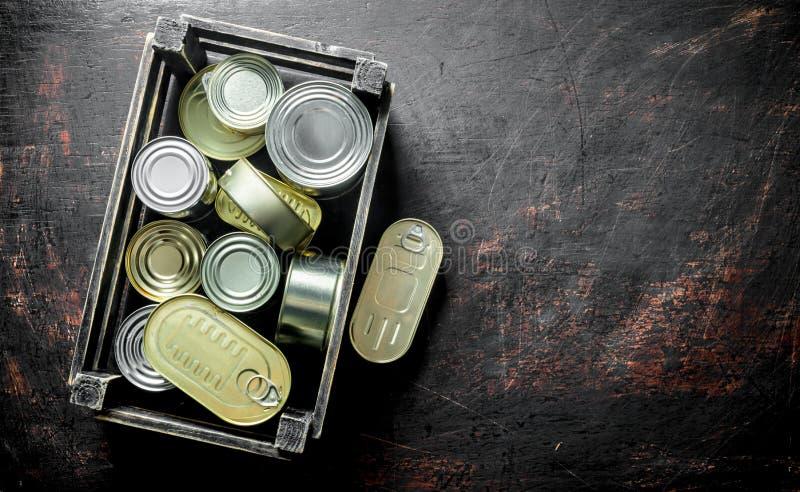 Grupo de latas cerradas de aluminio con la comida enlatada en una caja fotografía de archivo