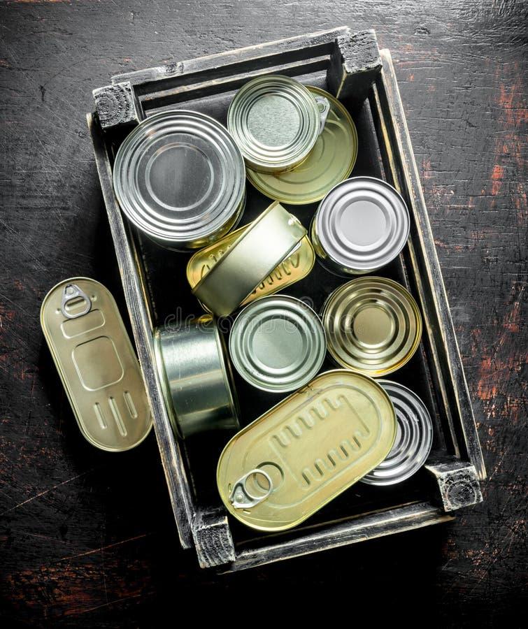 Grupo de latas cerradas de aluminio con la comida enlatada en una caja fotos de archivo libres de regalías