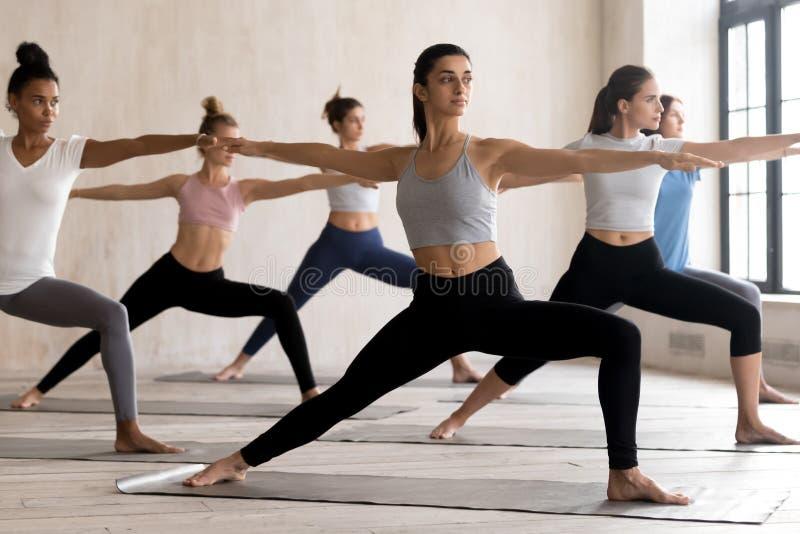 Grupo de lección practicante de la yoga de la gente joven que hace al guerrero 2 fotos de archivo