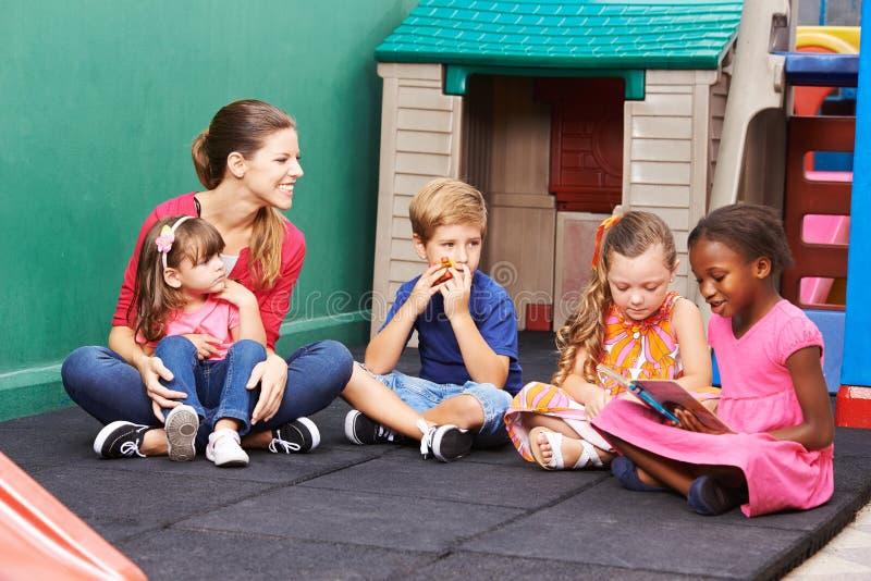 Grupo de livro de leitura das crianças no pré-escolar imagem de stock royalty free